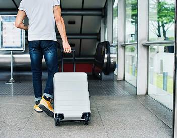 brantford home buying specialist walking into airport with his suticase as he prepares to head for vacation